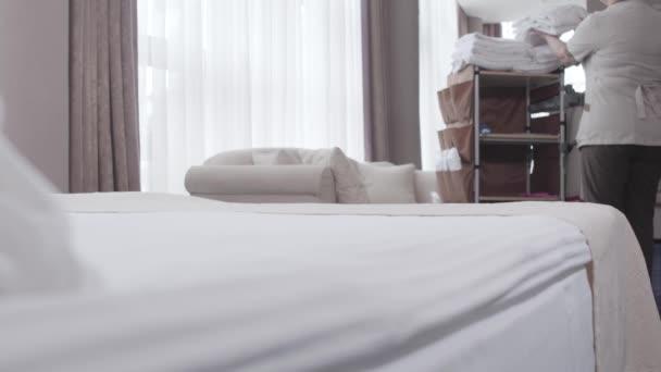 Profesionální pokojská, která dává čisté bílé župany na obě strany postele v hotelovém pokoji. Dospělá blondýna běloška v uniformě pracující v turistickém letovisku. Životní styl, zaměstnání, služby, práce.