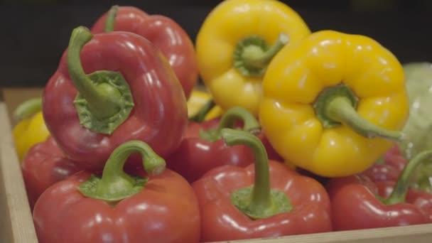 Egy közeli kép a piros és sárga paprikáról, ami a polcon fekszik az élelmiszerboltban. Színes zöldségek eladó a kiskereskedelmi üzletben. Vegán kaja, egészséges evés, harangbors. S-log 2.