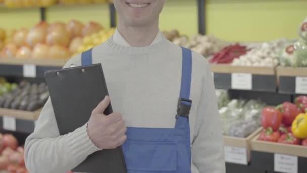 Ein bis zur Unkenntlichkeit lächelnder Kaukasier steht mit Aktenordner im Supermarkt. Eine erwachsene Supermarkt-Angestellte in blauer Uniform posiert im Gemüseladen. Handel, Beruf, Lebensstil, Geschäft. S-Log 2.