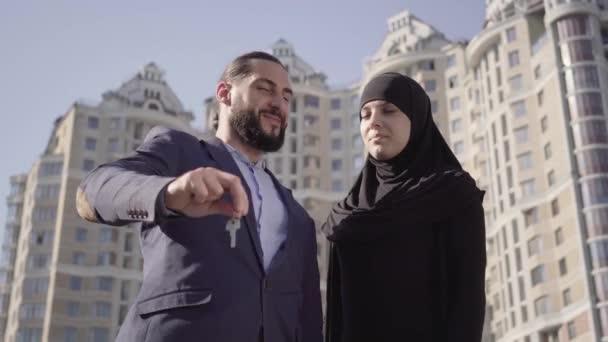 Portré boldog muszlim család hencegő kulcsok az új lakás. Sikeres gazdag férfi és nő hidzsábon áll a háttérben a felhőkarcoló a szabadban, és mosolyog. Vásárlás, vagyon, életmód.