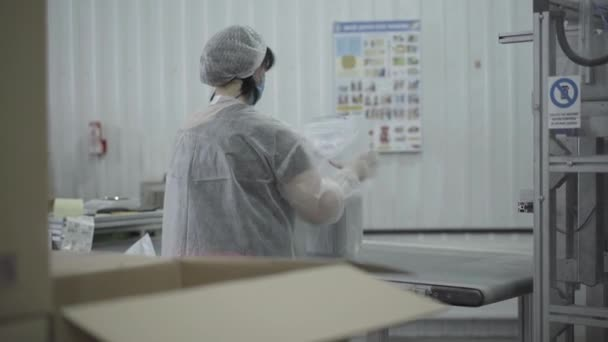 Back view of Caucasian woman packing finished food dish containers on production line. Professional female employee in protective uniform working next to automated machine. Industry, manufacture.