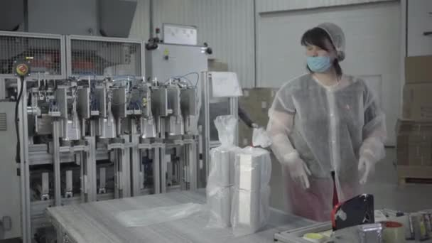 Serious woman in face mask packing finished products on production line and consulting confident man. Professional employees working in factory with automated equipment. Conveyor, manufacturing.
