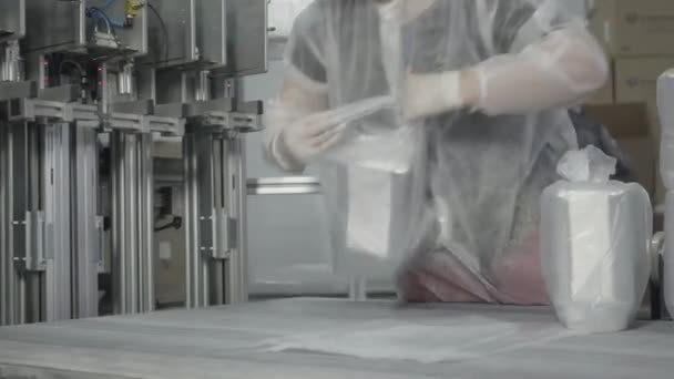 Adult Caucasian woman in face mask packing containers in transparent packages. Portrait of professional Caucasian employee working in factory on production line. Covid-19 manufacturing, industry.