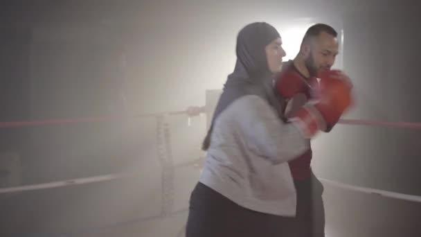 Seitenansicht einer konzentrierten muslimischen Frau, die im Gegenlichtnebel Bewegungen des Trainers auf dem Boxring wiederholt. Porträt einer selbstbewussten jungen, schönen Boxerin, die im Dunst im Linsenschlag trainiert. Sport, Kampfkunst