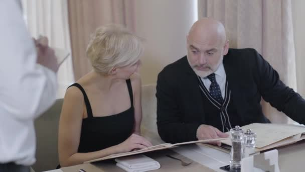 Wealthy Caucasian husband and wife making order in cafe. Portrait of happy man and woman discussing food from menu with unrecognizable waiter in restaurant. Lifestyle, leisure, dining, family.