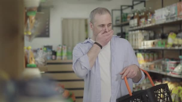 Tired male customer yawning as looking through grocery shelves. Portrait of adult Caucasian man buying products in food shop. Concentration, tiredness, consumerism, lifestyle.