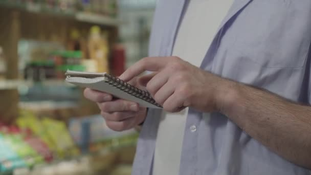 Unrecognizable adult man checking shop list in notebook. Side view of male customer buying products in grocery. Consumerism, lifestyle, healthy eating, dieting.