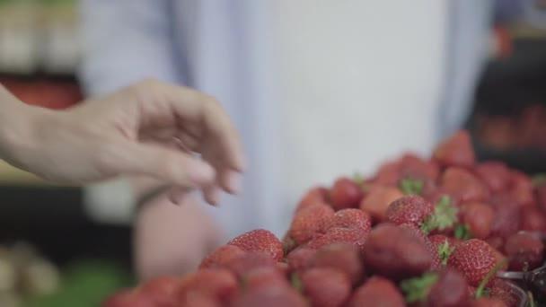 Muž a žena Kavkazské ruce se navzájem dotýkají, jako by brali jahody z police v supermarketu. Mladý muž a žena se omylem dotkli potravin. Flirt, setkání, životní styl.