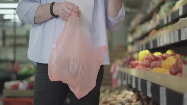 Male hands putting yellow tomatoes in plastic bag. Unrecognizable male buyer gathering vegetables in grocery. Concept of healthy vegetarian food, vegan lifestyle, consumerism.