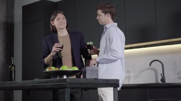 Porträt eines fröhlichen homosexuellen Paares, das sich in der Küche zur Musik bewegt und die Gläser klirren lässt. Junge kaukasische Männer tanzen zu Hause und feiern Jubiläum. Freude, Lebensstil, Freizeit, Beziehung.