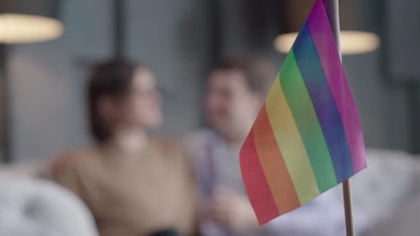Rainbow lgbt flag at front and blurred gay couple talking at the background. Symbol of same sex love with happy Caucasian boyfriends chatting. Equality, lifestyle.