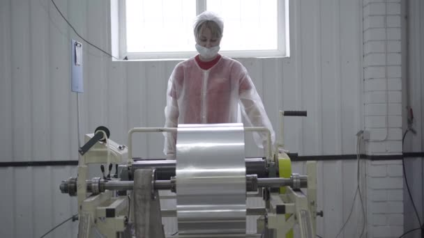 Young Caucasian woman in face mask and uniform controls process of aluminium foil rolling at factory. Portrait of professional female employee machine operator working on Covid-19 pandemic.