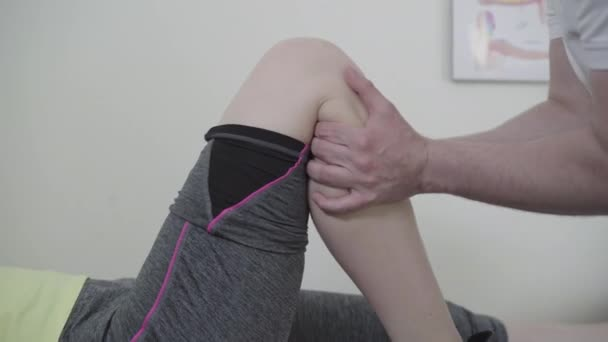 Side view of male hands checking knee of young Caucasian sportswoman. Unrecognizable traumatologist examining trauma of young sportive woman in hospital. Medical examination, traumatology.