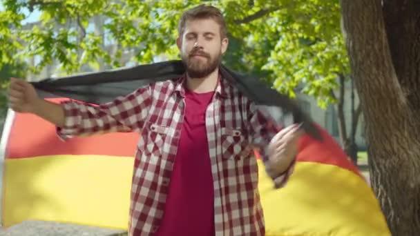 Kamera se blíží k sebevědomému vousatému vysokoškolskému studentovi, který se balí do německé vlajky. Portrét pozitivního pohledného mladého muže pózujícího s národním symbolem na školním dvoře za slunečného dne.