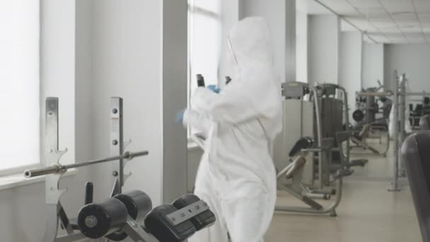 Funny dance of positive Caucasian woman in protective suit and respirator in gym. Portrait of cheerful young Caucasian woman dancing in sports club on Covid-19 pandemic lockdown.