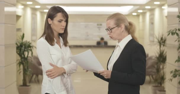 Angry mid-adult CEO scolding young female employee in business center and leaving sad Caucasian woman with documents in hall. Conflict of employer and white-collar worker. Cinema 4k ProRes HQ.