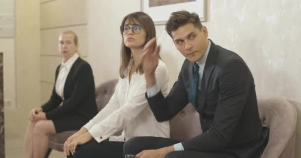 Nervous men and women sitting in office hall waiting. Portrait of stressed Caucasian employees in business center before meeting or project discussion. Cinema 4k ProRes HQ.