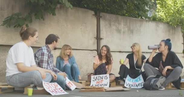 Wide shot of positive demonstrators resting after protest with pizza. Laughing young Caucasian men and women sitting with anti-racism placards and chatting. Cinema 4k ProRes HQ.