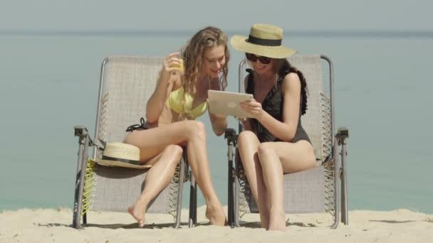 Két boldog fiatal nő portréja fürdőruhában, táblagéppel a homokos parton beszélgetve. Gyönyörű magabiztos kaukázusi turisták élvezik nyaralás nyári üdülőhelyen. Gazdag hölgyek napoznak a napozóágyakon..