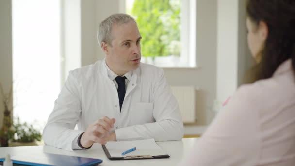 Seriöser Arzt im Gespräch mit Patient im Krankenhaus. Porträt einer angesehenen kaukasischen Ärztin, die eine Frau nach einer medizinischen Untersuchung berät. Mittlerer Erwachsener arbeitet mit Klient in Klinik.