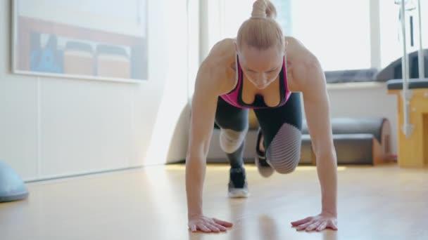 Sebevědomá soustředěná sportovkyně cvičí prkna v tělocvičně. Portrét atleticky blonďaté bělošky trénující v interiéru. Pozitivní sportovní dámské cvičení. Sportovní koncept.