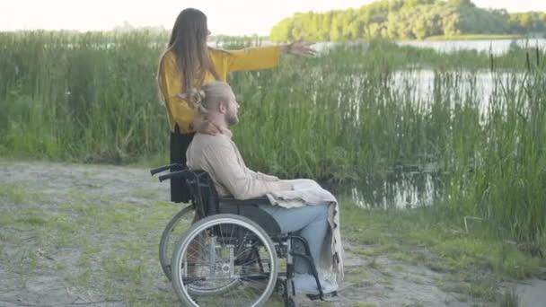 Seitenansicht einer jungen kaukasischen Frau, die mit einem gelähmten Mann im Rollstuhl am Flussufer steht und spricht. Weitschuss von querschnittsgelähmtem Freund, der Sommerabend mit Freundin im Freien genießt.