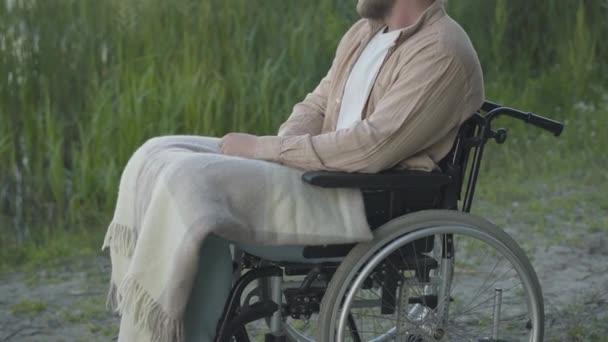 Unerkennbarer Mann mit verletzten Beinen, der draußen im Rollstuhl sitzt und denkt. Seitenansicht eines querschnittsgelähmten Kaukasiers, der sich an einem Sommerabend allein im Park ausruht. Behinderten- und Gesundheitskonzept.