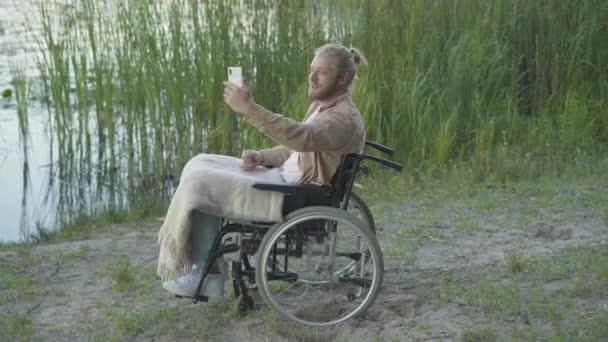Seitenansicht eines positiven behinderten Mannes im Rollstuhl, der per Videochat mit einer Selfie-Kamera auf dem Smartphone spricht. Lächelnde kaukasische Männchen chatten online und ruhen sich am Flussufer im Freien aus.