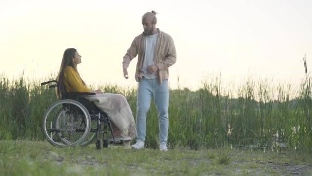 Weitschussbild eines wütenden Mannes, der einer behinderten Frau den Ehering zurückgibt und geht. Die deprimierte schöne kaukasische Invalidin schließt ihr Gesicht mit weinenden Händen. Trennung und Scheidung, Behinderung.