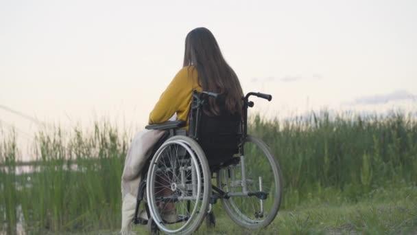 Rückenansicht einer einsamen Frau im Rollstuhl, die am Flussufer sitzt. Weite Aufnahme einer brünetten kaukasischen behinderten Dame, die den Sommerabend allein im Freien verbringt. Einsamkeit und Behinderung.