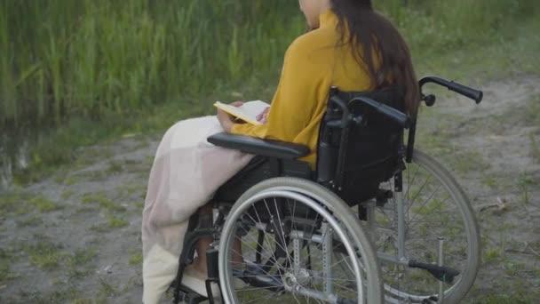 Rückenansicht einer positiv behinderten jungen Frau, die im Freien Bücher liest. Selbstbewusste kaukasische Dame im Rollstuhl genießt Sommerabend im Park mit Literatur. Lebensstil und Selbstbewusstsein.