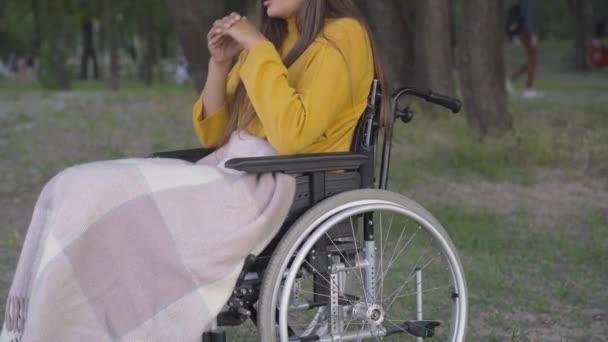 Eine junge, bis zur Unkenntlichkeit querschnittsgelähmte Frau sitzt im Rollstuhl im Park und denkt. Kaukasischer Behinderter, der einen einsamen Sommerabend im Freien verbringt. Behinderung und Einsamkeit.