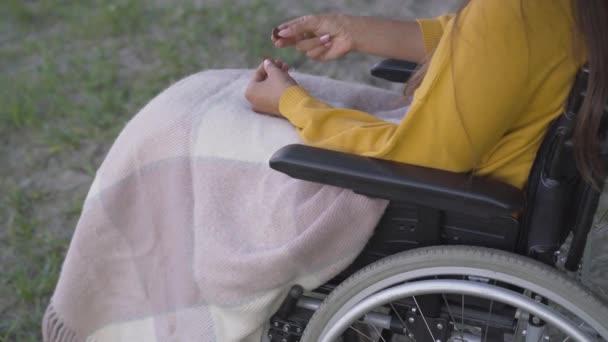 Eine unkenntliche junge Frau im Rollstuhl, die draußen Münzen zählt. Arme, gelähmte kaukasische Invaliden, die wenig Geld haben. Soziale Probleme behinderter Menschen.