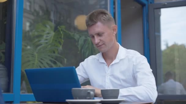 Portrait of young Caucasian man checking mail in outdoor cafe. Successful confident businessman messaging online using laptop. Coffee break of handsome busy male CEO.