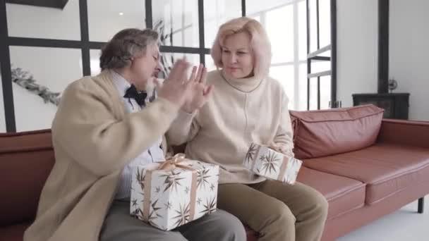 Radostný bělošský pár důchodců dává plácnutí na dovolenou. Portrét šťastného staršího muže a ženy oslavující Silvestra s vánočními dárky. Koncept oslavy.