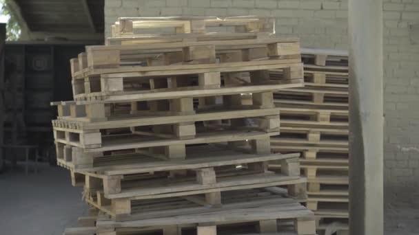 Fából készült raklapok széles választéka halmozódott fel a szabadban a gyártási helyszínen. Áruraktárak raklapjai.