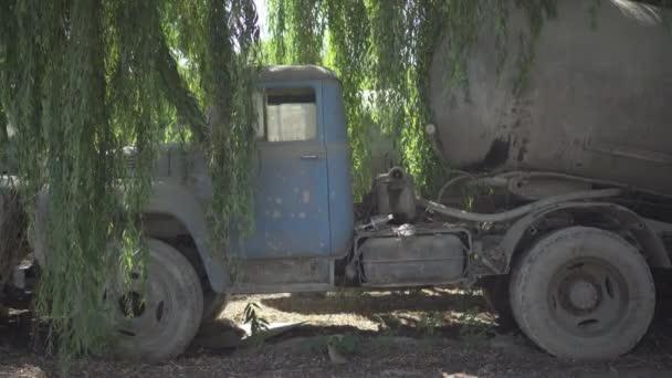 Seitenansicht eines kaputten Betonmischer-LKW, der auf einer zerstörten Fabrik im Freien steht. Alte, desolate Industrietransporte an verlassenen Produktionsstätten an sonnigem Tag.