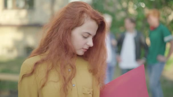 Close-up of young charming redhead woman turning to camera and smiling. Portrait of beautiful Caucasian university student posing on campus outdoors with blurred people at the background.
