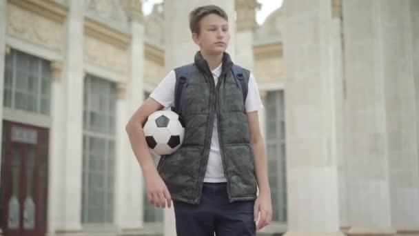 Aranyos iskolás, hátizsákkal és labdával körülnéz és integet. Portré pozitív kis kaukázusi fiúról, aki foci vagy foci felszereléssel a szabadban áll. Sportkoncepció.