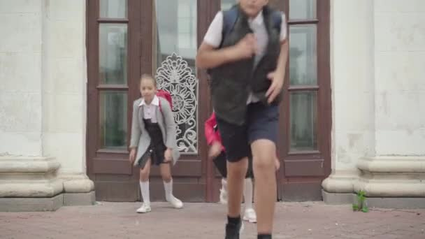 Iskolából tanítás után elszökő gyerekek. Pozitív kaukázusi fiú és lányok élvezik a tanulás végét. Boldog gyerekek szórakoznak. Z generációs életmód.