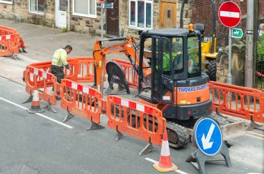Roadworks in a street with digger, barriers and workmen.