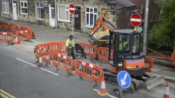 Pipe laying roadworks. Workmen and digger. High angle view.