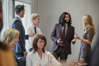 Businessmen and women meeting and greeting each other at a business meeting.