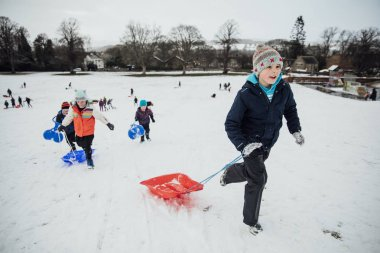 Children from the community are running up a hill to have a race together on sleds in the snow.