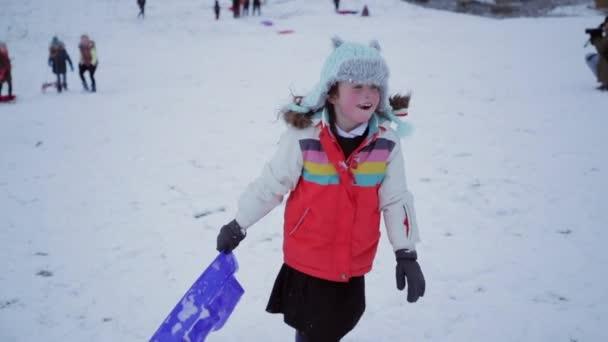 Kleines Mädchen läuft im Schnee den Hügel hinauf und zieht einen Schlitten.