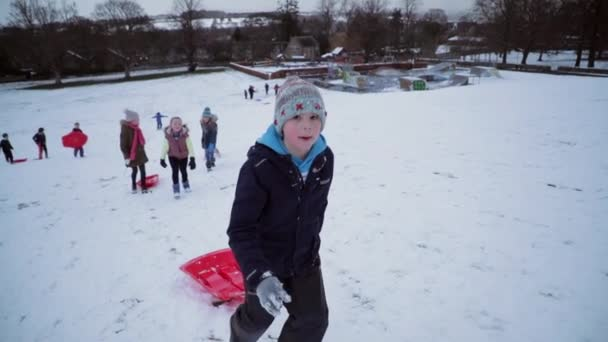 Kleiner Junge und seine Freunde laufen einen großen Hügel im Schnee hinauf, um ein Schlittenrennen zu veranstalten.
