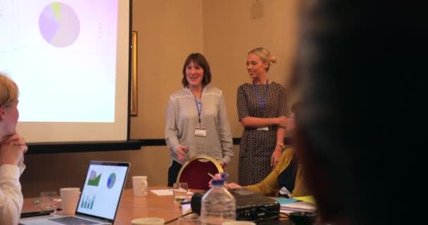 Přes rameno pohled na skupinu podnikatelů kladení otázek v rámci konference předvádějící prezentaci.