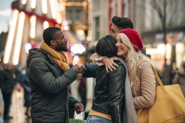 Side view of two couples saying goodbye to each other on the city street. The two men are shaking hands and the two women are hugging each other.