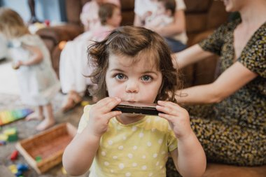 Front view of a little toddler girl looking at the camera. She is having fun and playing the harmonica. In the background ther are other children playing and her mother is sat down next to her.
