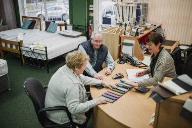 Senior couple are buying a new bed and are paying at a desk with a sales clerk. They are deciding on the design with color swatches.